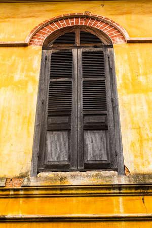 Vintage windows on old yellow brick wall photo