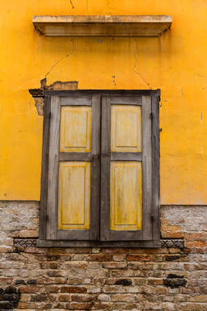 Wooden yellow window in old yellow colonial building on old brick wall with cracked stucco layer background Stock Photo