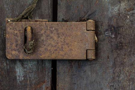 Closeup of old rusty door hinge on wooden door