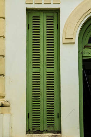 Green vintage wooden windows, colonial style building from Vientiane, Laos