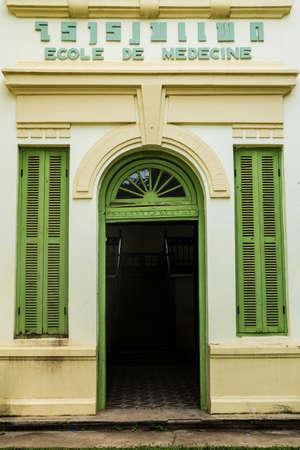 緑のビンテージ木製窓と黄色の壁、植民地様式のビエンチャン、ラオスから建物のドア