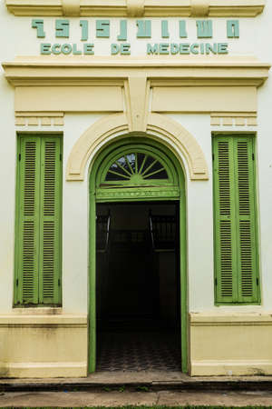 Green vintage wooden windows and door on yellow wall, colonial style building from Vientiane, Laos