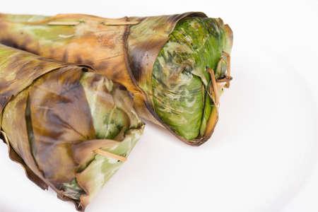 もち米のロースト、バナナの葉と白い背景に包まれました。 写真素材