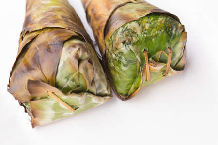 Sticky rice roast , wrapped in banana leaves and white background.