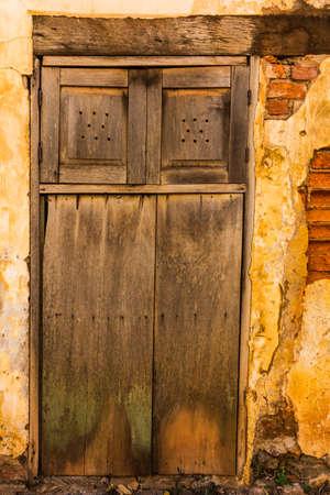 木製のドアで古いレンガの壁