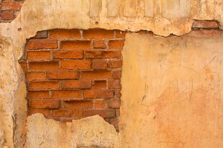 ひびの入った漆喰で古いレンガの壁