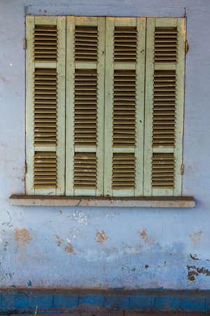 古い家の青い閉じたシャッターと古い窓。ビンテージ バック グラウンド テクスチャ。