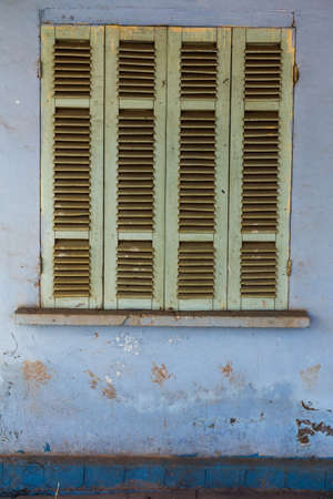 The old window with blue closed shutters on an old house. Vintage background, texture. Stock Photo