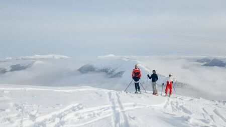 People observing mountain scenery. These are skiers, they dressed in winter sport jackets and have skies attached.