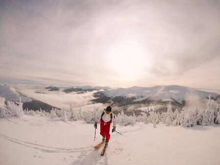 Skier, skiing. Rises to high mountains against the sunset, Ukraine