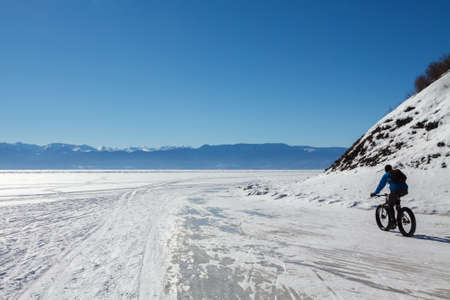 cycler: A cycler is riding on the ice of Baikal lake Stock Photo