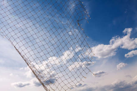 fish net: Fish net on blue sky with clouds Stock Photo