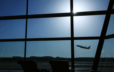 airport window: An airplane is taking off behind the airport window Editorial