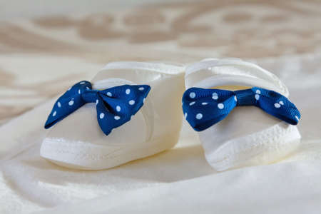 White babys bootees with blue bow on a white sheet