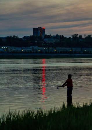 gloom: Boy fishing at river bank Stock Photo