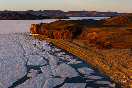 Sunrise at Baikal lake with cracking ice