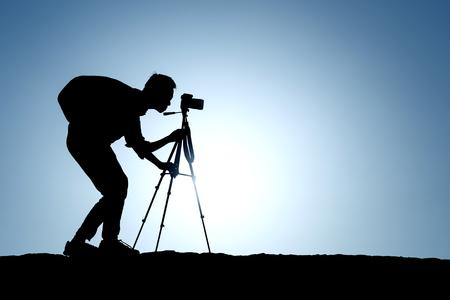 Eine Silhouette eines Fotografen mit Stativ