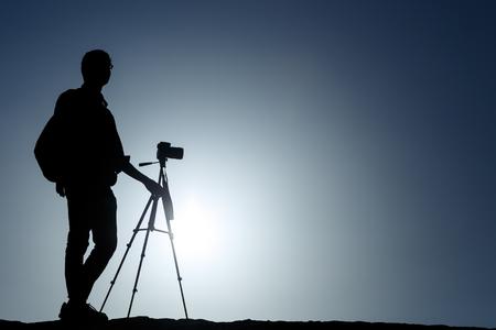 Un fotógrafo con trípode con sol y cielo azul.