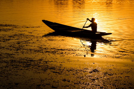 Silhouette of a man peddling in a boat at sunset