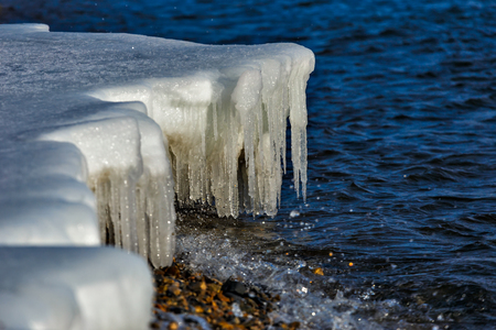 Icicles at the shore of Baikal lake in December 免版税图像