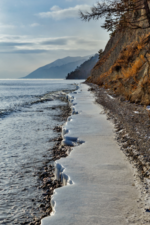 Coastline of Baikal lake in December with water and ice Фото со стока