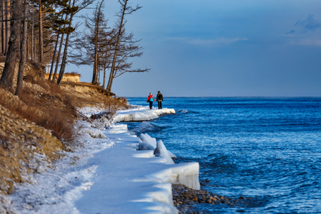 Two people walking on the shore of Baikal lake in winter
