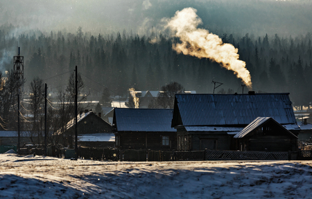 Russian village in winter with fog and smoke from chimneys