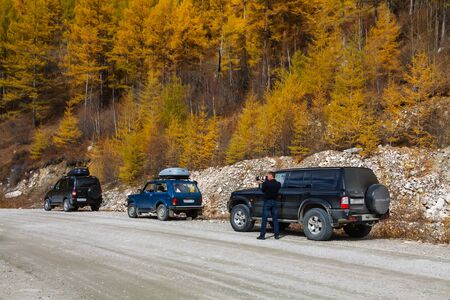 ORLIK, BURYATIYA, RUSSIA - SEPTEMBER 2014: A photographer taking pictures at the gravel road with three cars and yellow larch trees
