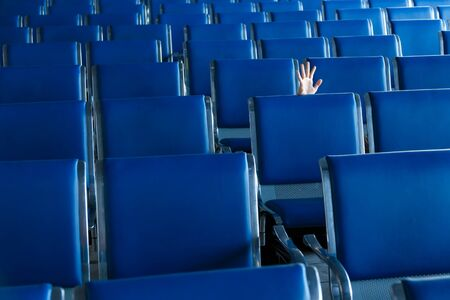 Row of blue seats and a human hand at the airport hall Stock Photo