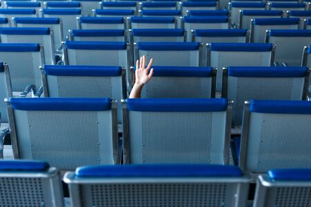 Row of seats and a human hand in help gesture in airport hall