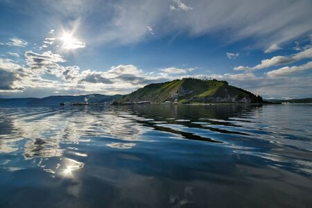 View of the Lake Baikal in summer with clouds and sun and their reflection in wavy water Banco de Imagens