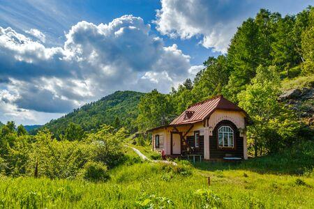 Old house on the Circum-Baikal Railway in Siberia on a cloudy sunny summer day Standard-Bild