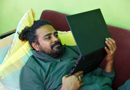 An Indian man lying on sofa and working on his laptop