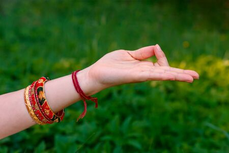 Woman hand in meditation mudra on a green meadow