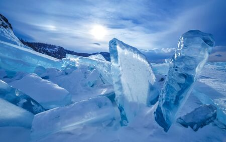 Blocks of broken blue ice on sky background with sun and clouds at Baikal lake