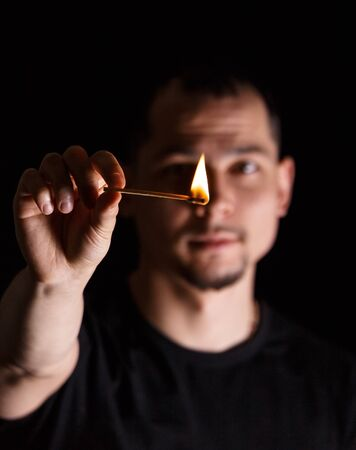 Man holding burning match stick in front of blurred face on dark background