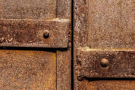 Part of rusty steel door with rivets and slot background