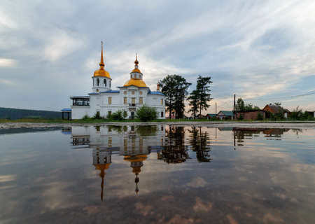 UST-KUDA, RUSSIA - 24 JUNE 2020: Russian rural landscape with an old church and its reflection in water Editorial
