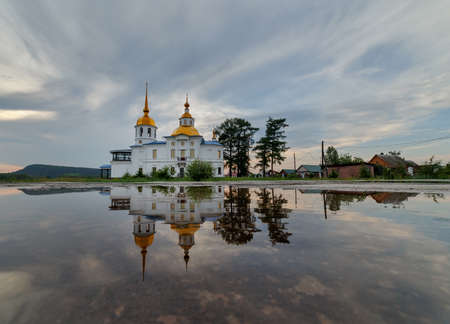 UST-KUDA, RUSSIA - 24 JUNE 2020: Russian rural landscape with an old church and its full reflection in water and cloudy sky