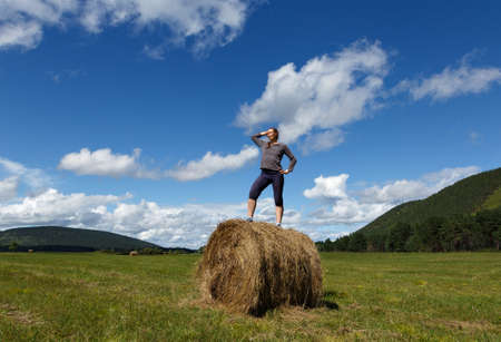 A woman in casual clothes standing on the top of a haystack in the middle on a field