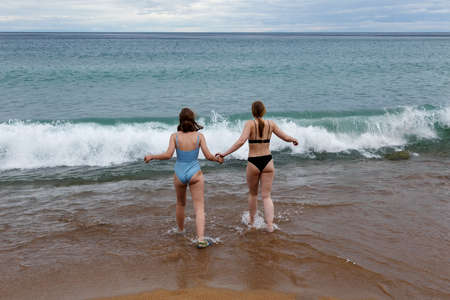 Girls teenagers holding hands in swimming suits on a beach of Baikal lake going to water in cloudy weather
