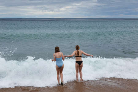 Girls teenagers holding going to swim on stormy weather at Baikal lake