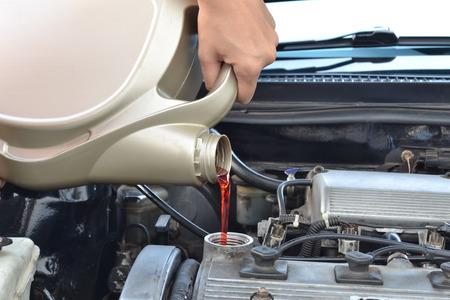 一環として、車のエンジンに新鮮な油を注ぐその