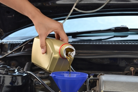 motors: Car servicing mechanic pouring oil to engine