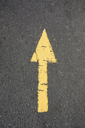 answers highway: asphalt road and arrows of old painted yellow.