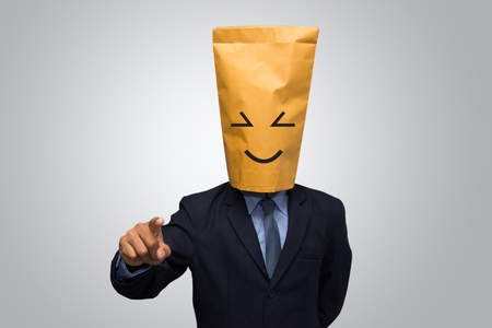 Businessman in smiling ecological paper bag on head.  photo