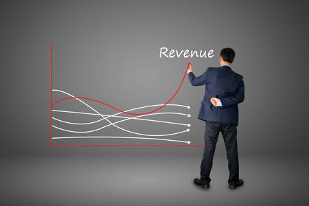 business hand writing revenue graph concept.  photo