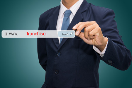 Business and technology, searching system and internet concept - male hand pressing Search franchise button.  Standard-Bild