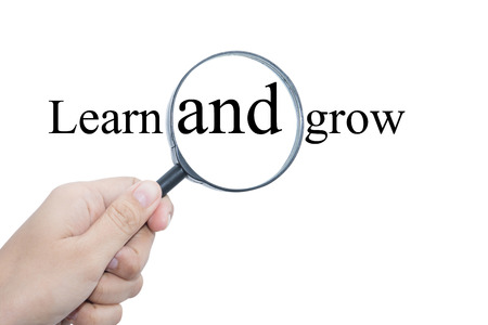 short phrase: Hand Showing Learn and grow Word Through Magnifying Glass  Stock Photo