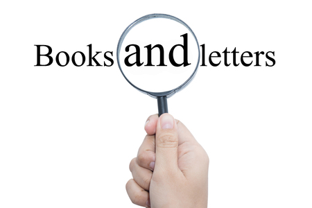illiteracy: Hand Showing Books and letters Word Through Magnifying Glass
